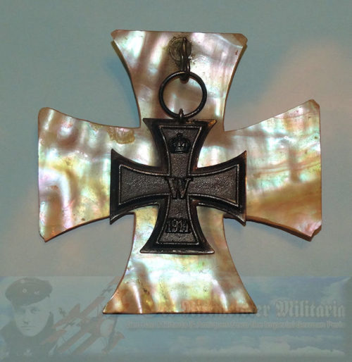 "Elegant and uniquely displayed 1914 Iron Cross 2nd Class. A mother-of-pearl shell section, measuring 3 ½"" x 3 ½,"" has been cut into the shape of an Iron Cross. It serves as a illuminating background or frame for an actual 1914 Iron Cross 2nd Class."