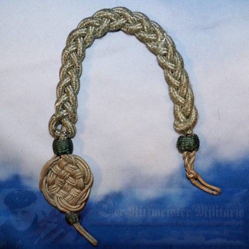 This is an officer aiguillette. It has three strands of gold bullion. Across these three strands, there are bands of what appear to be brown / black.